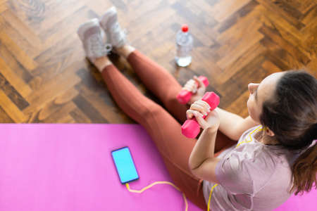 Young sporty woman exercising at home with dumbbells. Fitness, workout, healthy living and diet concept