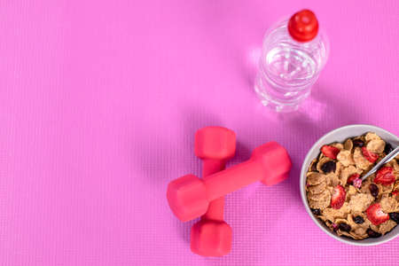 Diet and fitness concept with dumbbells and cornflakes on pink training mat Foto de archivo