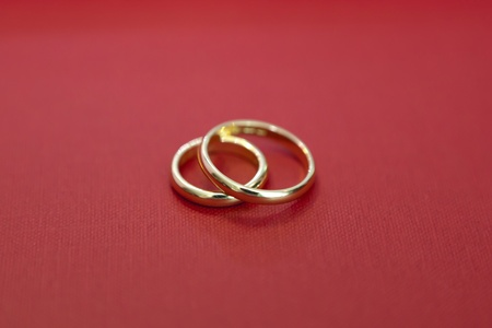 A close up of two beautiful wedding rings on red texture photo
