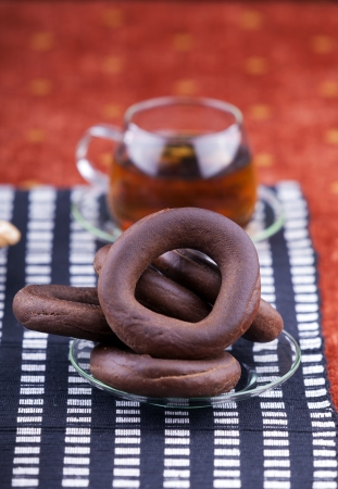 plate with pretzel next to a cup of tea studio shot photo