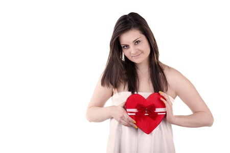 Smiling girl with a heart in her hands isolated on white studio shot Stock Photo