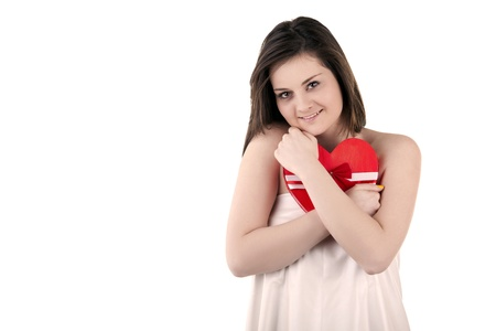 Gorgeous girl with a heart in her hands isolated on white studio shot photo