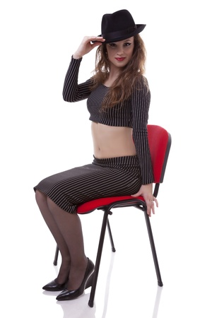 Sexy caucasian girl sitting on a red chair with a hat on her had isolated on white background studio shot photo