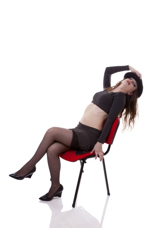 Sexy woman sitting on a red chair isolated on white background studio shot photo