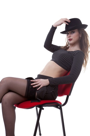 Sexy girl on a red chair isolated over white studio shot photo