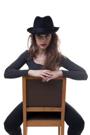 Sexy girl sitting on a chair wearing a hat isolated on white background studio shot photo