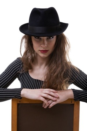 Artistic photo of a girl sitting on a chair with a hat on her had isolated on white studio shot photo
