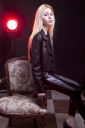 Girl in leather jacket with a red light behind sitting next to a vintage chair studio shot photo