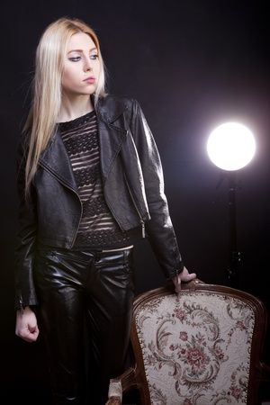Sexy blonde next to a vintage chair on a black background studio shot photo