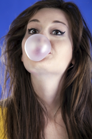 Girl with bubble gum on blue background studio shot photo
