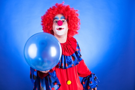 Smiling clown in studio shot on blue background
