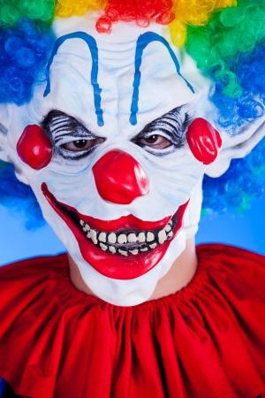 Enge clown persoon in clown masker op blauwe achtergrond studio opname