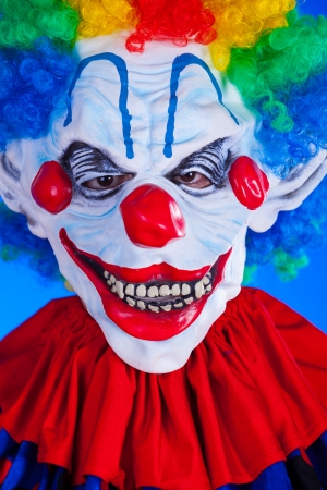 Scary clown person in clown mask on blue background studio shot photo