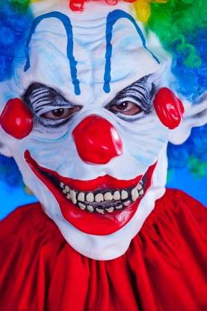 Scary clown person in clown mask on blue background studio shot