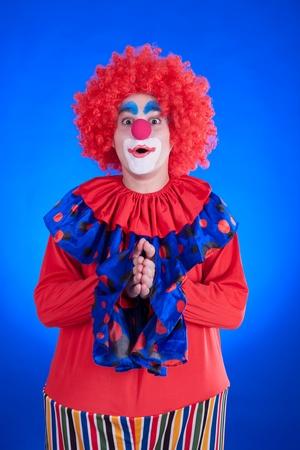 Clown on blue backgound studio inside shot Stock Photo