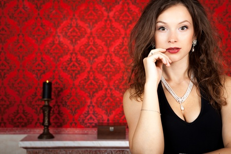 Sensual glamour girl on red vintage background inside studio shot photo