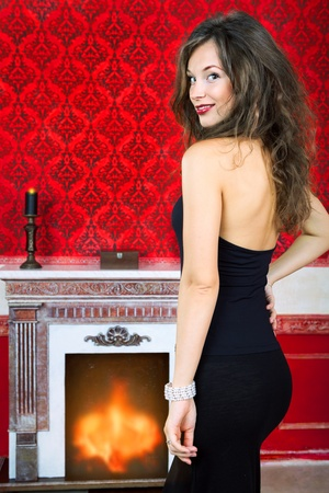 Sensual woman next to a fireplace in vintage room inside studio shot Stock Photo