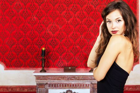 gorgeous girl in black dress posing in a vintage room on a red background inside studio shot photo