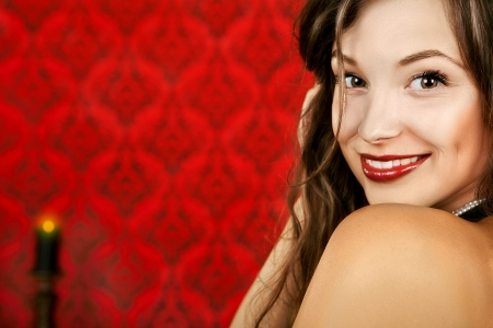 Smiling sensual girl on a red vintage background with a burning candle studio luxury shot photo