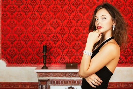 Fashion glamour woman on red vintage wall with a burning candle skin care, vintage rococo interior red walls and candle, model posing photo