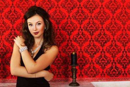 Mooi meisje met luxe sieraden op rode vintage achtergrond in een studio opname, luxe, kunst, glamour en mode schieten