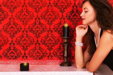 Girl and canles romatic fashion glamour woman looking at two candles on a fireplace inside a vintage red studio