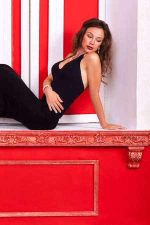 Gorgeous sexy woman in evening dress on a sill in red vintage room glamour fashion style photography photo