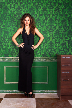Studio fashion glamour shooting of a beautiful woman on a green vintage wall in evening dress with luxury jewellery