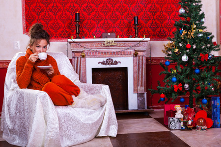 Woman with a cup of tea inside a red vintage room next to a christmas tree studio shooting photo