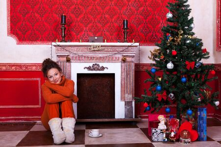 Beautiful girl inside a red vintage room with christmas decor studio shooting