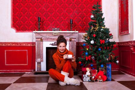 Beautiful girl inside a red vintage room with christmas decor studio shooting photo