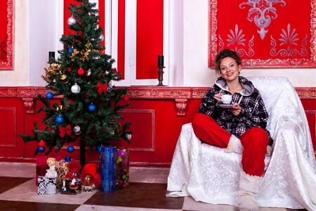 Girl in worm clothes inside a red vintage room with christmas decoration studio shooting Stock Photo - 22619758