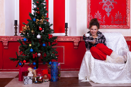 Girl in worm clothes inside a red vintage room with christmas decoration studio shooting photo