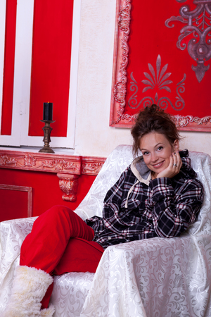 Girl in worm clothes inside a red vintage room with christmas decoration studio shooting