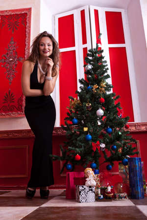 Gorgeous girl in evening dress in red vintage room with christmas decoration studio shot