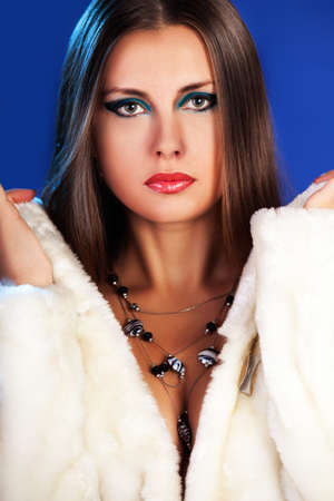 Sexy woman in fur with jewellery on blue winter background fashion glamour studio photography photo
