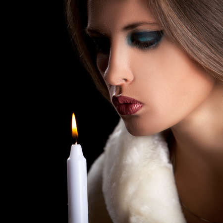 Sensual woman in fur blowing a candle Stock Photo