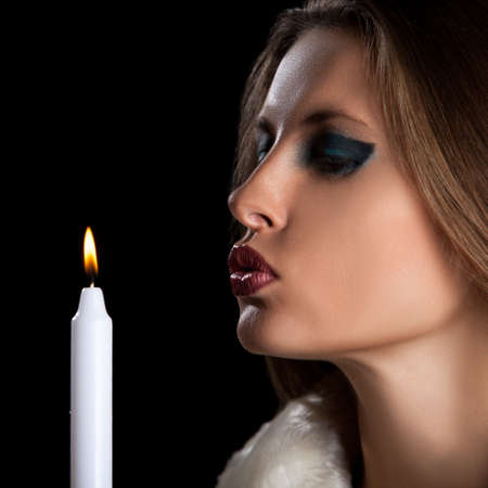 woman blowing: Beautiful woman in winter fur blowing a candle Stock Photo