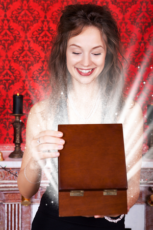Gorgeous smiling woman opening a wooden box in a red vintage interior. New year and christmas theme. Luxury interior and expesive jewellery photo