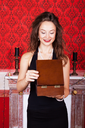 Gorgeous rich woman in expesive vintage room opening a wooden gift box. Merry Christmas and Happy New Year Theme. Luxury, rich and expesive interior. photo