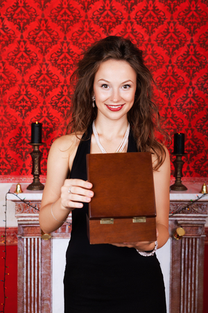 Smiling girl opening a wooden gift box and smiling at camera studio shooting. Luxury and vintage interior. photo