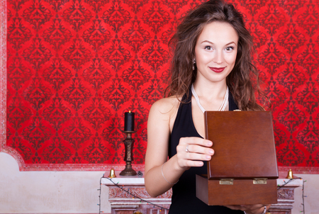 Smiling girl in evening dress opening a gift wooden box in red vintage interior. Luxury and vintage room photo
