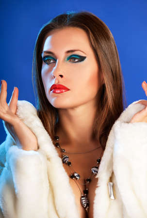 Sexy woman in winter fur on blue background fashion glamour style photography studio shooting photo