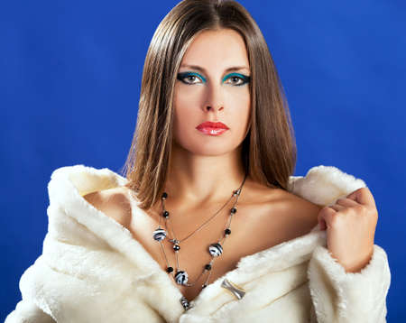 Sensual woman in white fur on blue background. Fashion Glamour style photography. Beauty and winter make up. Toned skin and luxury jewellery photo