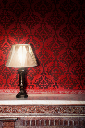 Vintage lamp on old fireplace in room with red rocco pattern. Luxury rocco interior Фото со стока