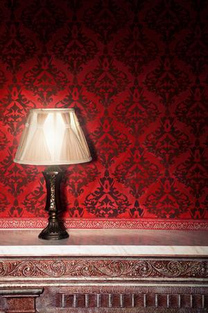 Vintage licht op de oude open haard in de kamer met rode rocco patroon. Luxe rocco interieur Stockfoto