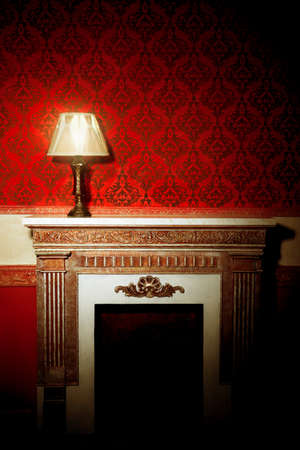Beautiful old lamp on fireplace in red vintage room Stock Photo