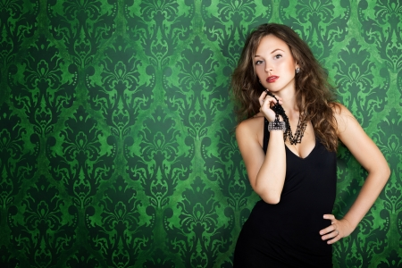 decolletage: Beautiful brunette model posing in green vintage room  Old interior with vintage pattern  Woman in evening dress with decolletage
