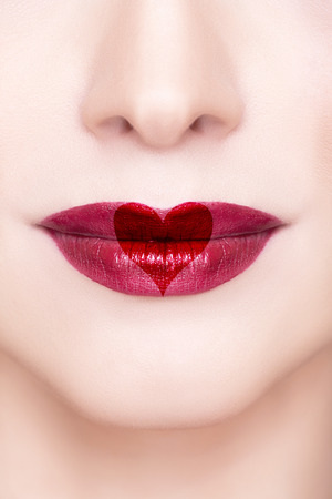Beautiful sensual red lips with heart shape macro shooting. Professional make up. Red lipstick. Toned and clean skin. Happy Valentine photo