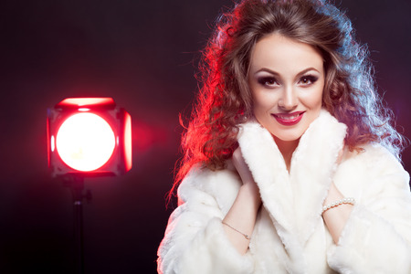 Beautiful woman in winter fur with red light behind on black  Rock star  Rich glamor and fashion concept  Studio lights photo